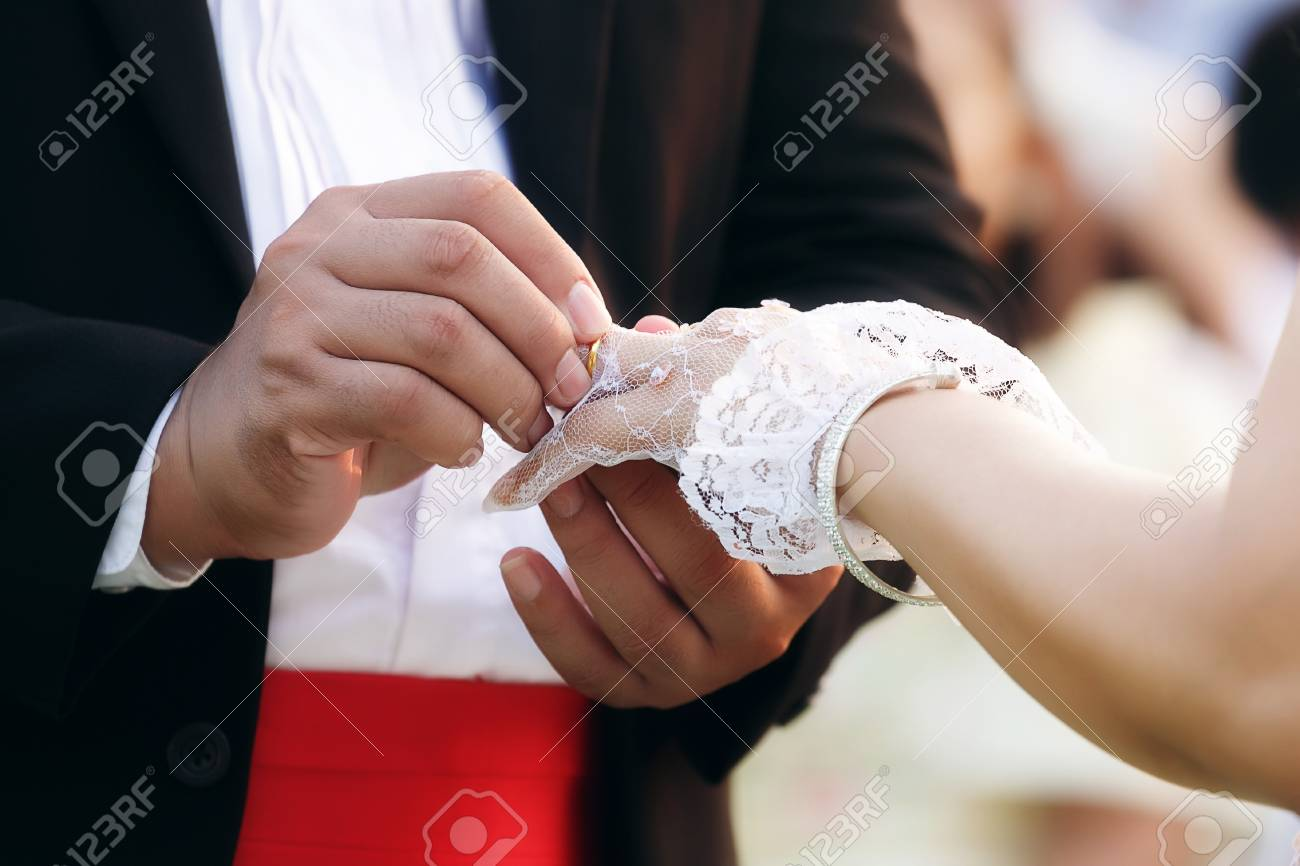 Groom Wears Wedding Ring On The Hand Of The Bride Stock Photo