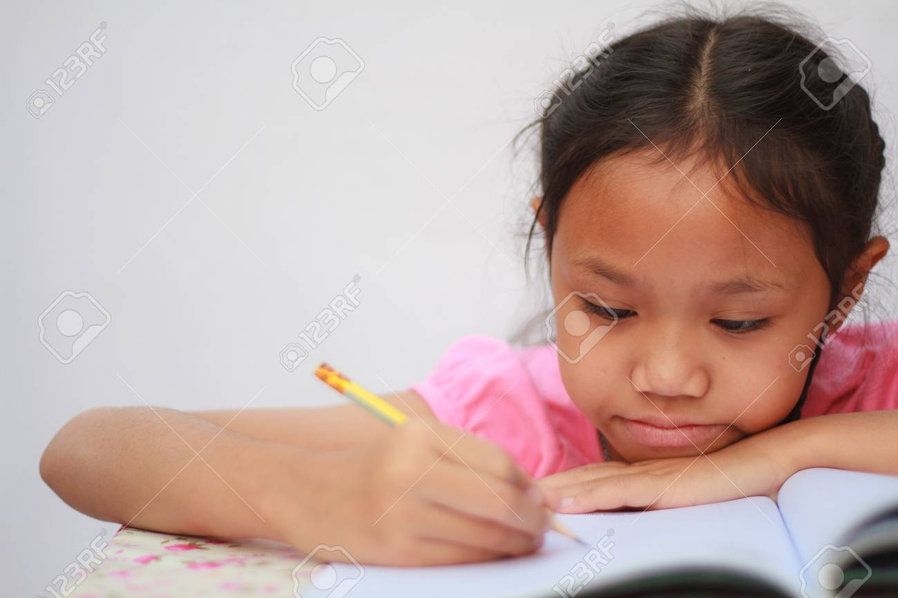 Girl writing a book with a pencil. Stock Photo - 25916926