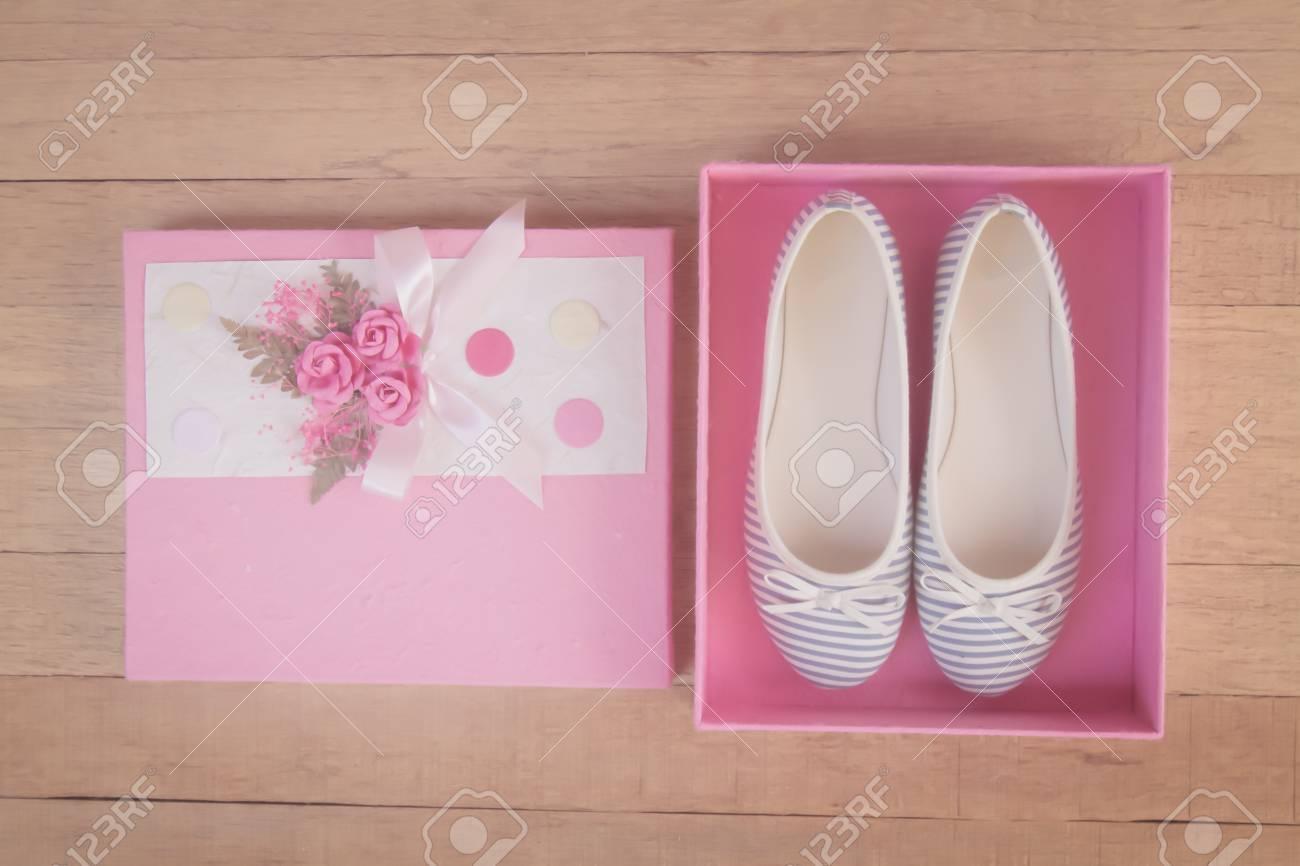 1b4e21dc4 Caja de regalo cargada con zapatos de niña con espacio de copia. Tono  vintage o