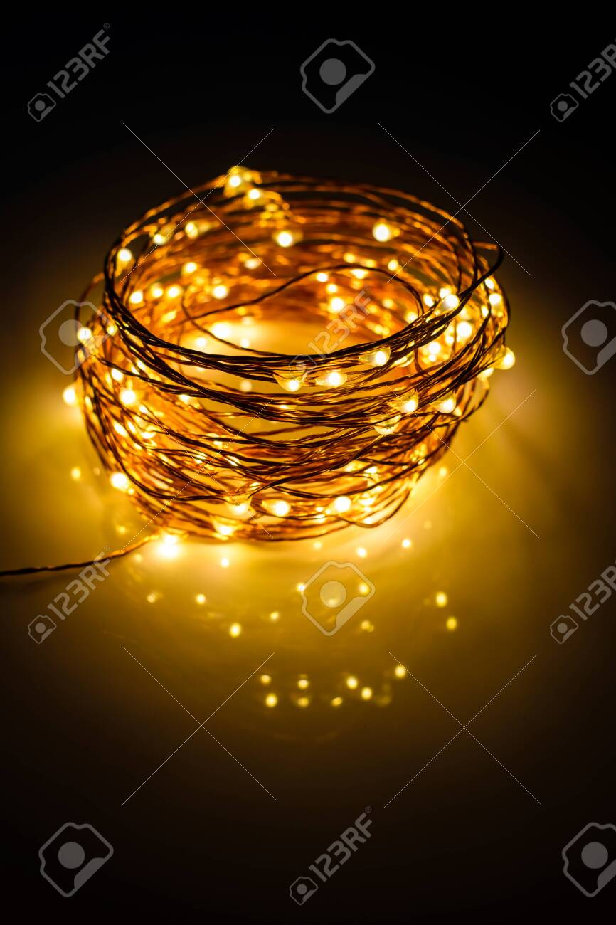 Yellow colored light chain for decoration placed on a reflective surface. Portrait view - 151406894