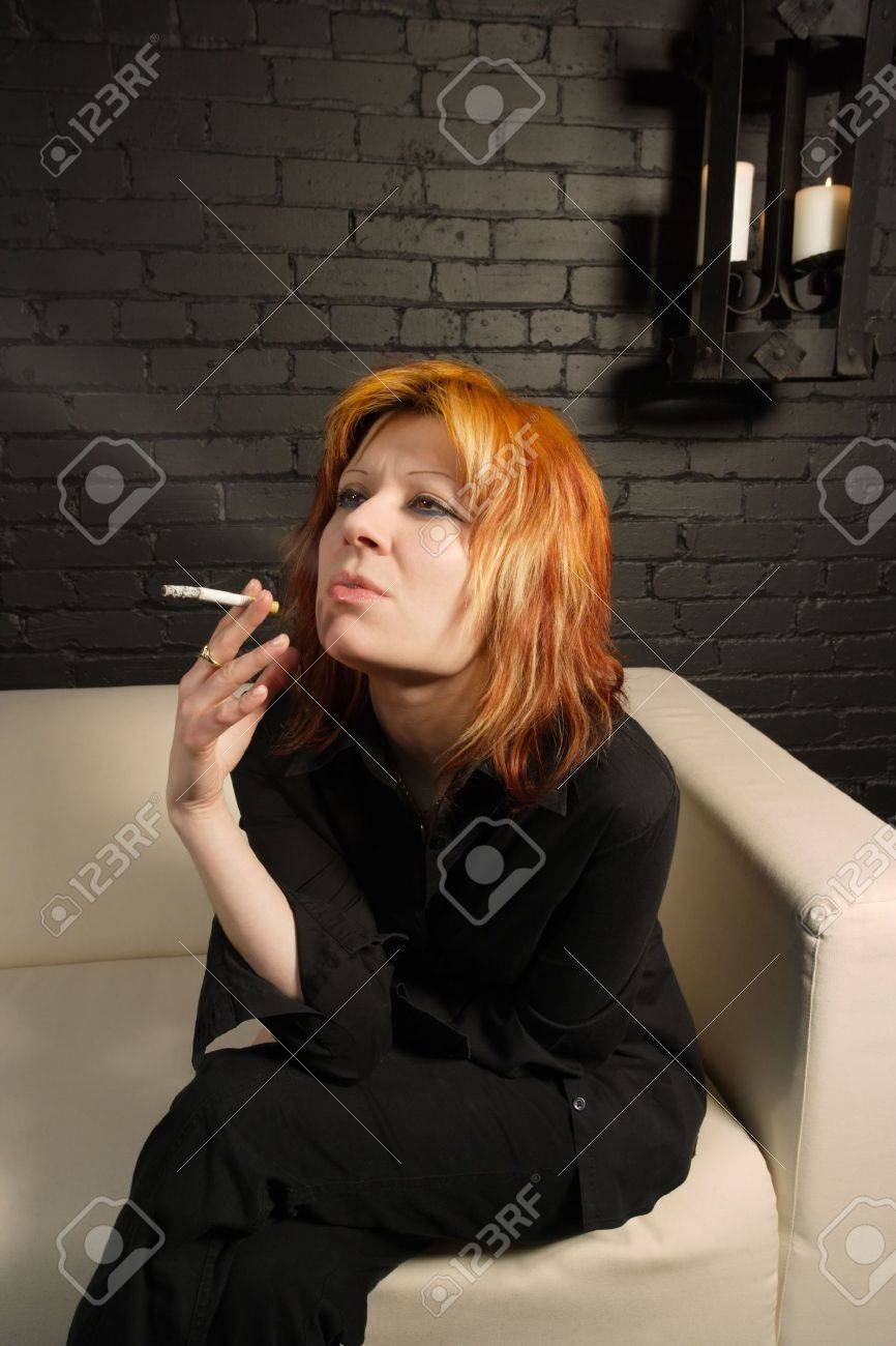 female with dyed orange hair sitting on a couch smoking a cigarette. Stock Photo - 819105