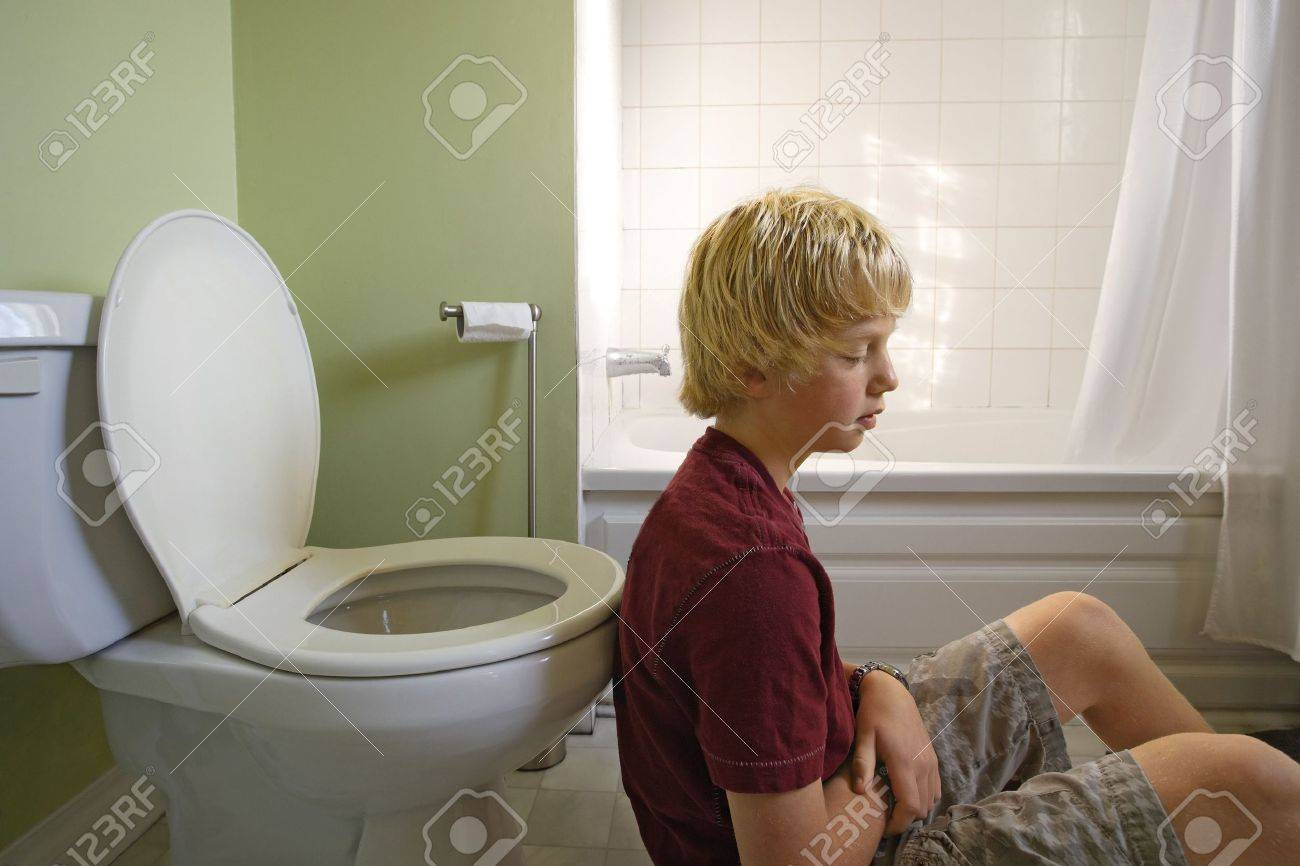 young boy and the toilets Stock Photo - A young boy suffering with a stomachache, leaning up against a toilet. Shot with natural light coming through a window.