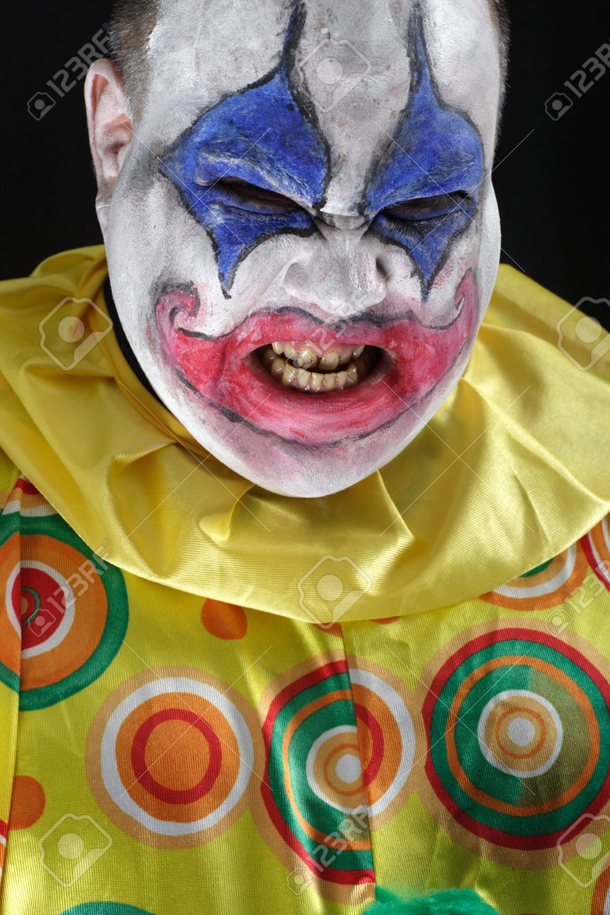 A nasty evil clown, angry and looking mean. Harsh lighting from below, focus on the teeth. Stock Photo - 5983706