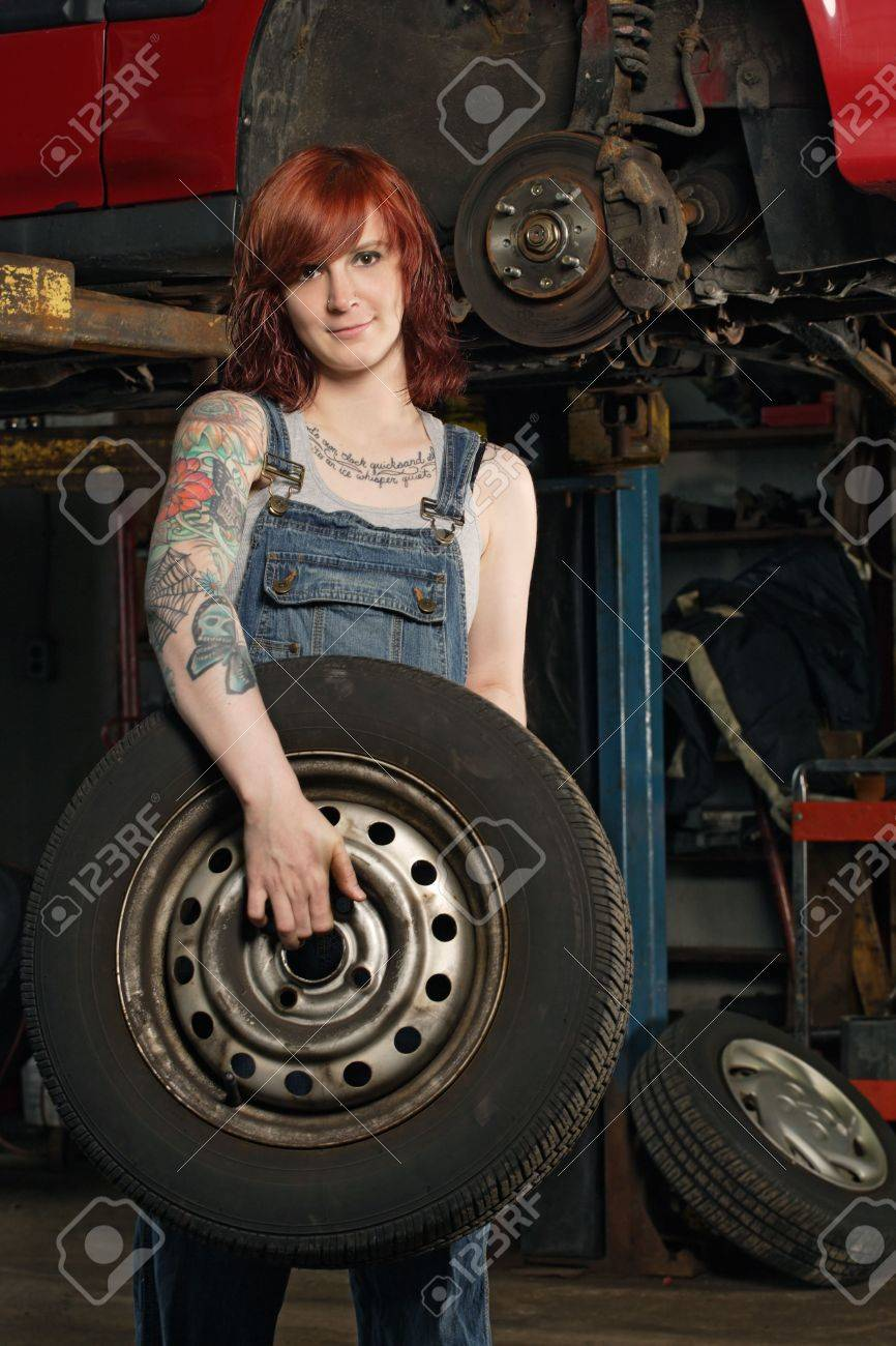 Photo of a young beautiful redhead mechanic wearing overalls and holding a wheel.  Attached property release is for arm tattoos. Stock Photo - 7475029