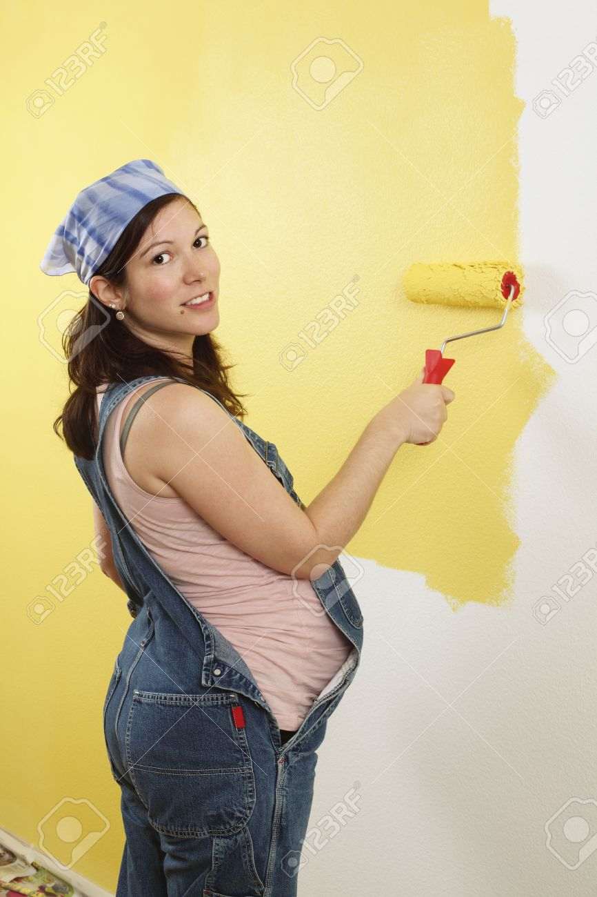 Photo of a pregnant female painting the wall of a bedroom for her future baby. Stock Photo - 9438873