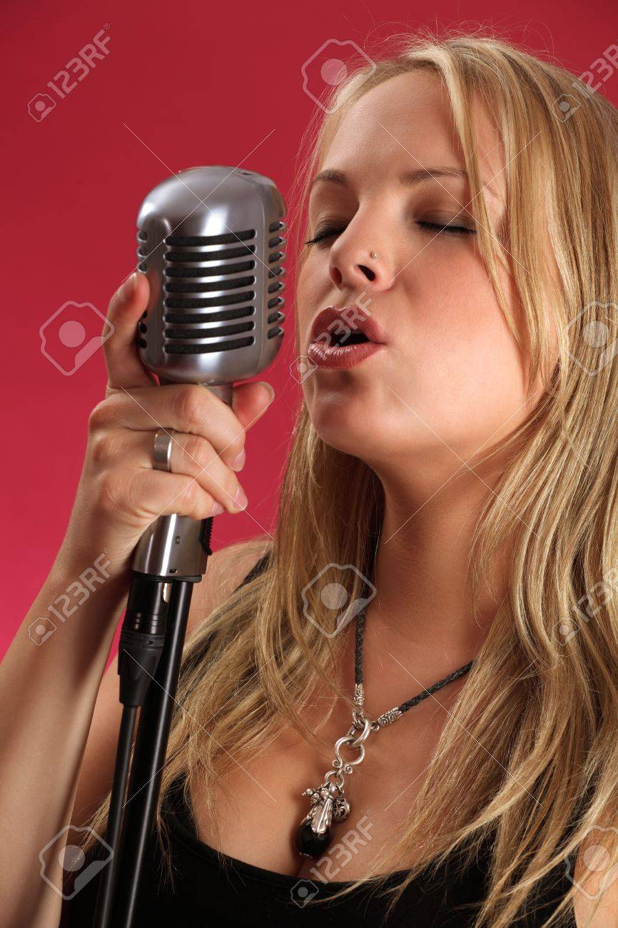 Photo of a beautiful young blond singing into a vintage microphone. Stock Photo - 10307633