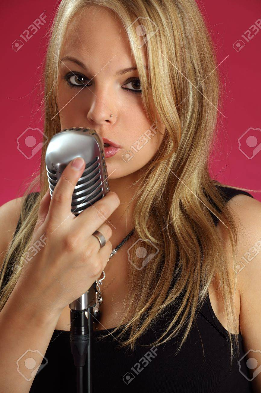 Photo of a beautiful young blond singing into a vintage microphone. Stock Photo - 10307625