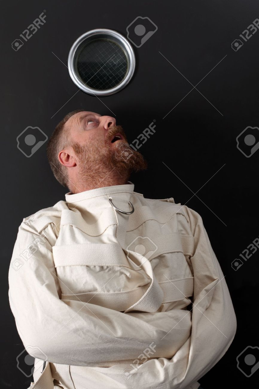 Photo of an insane man in his forties wearing a straitjacket crouched below the window of his cell. - 11873038