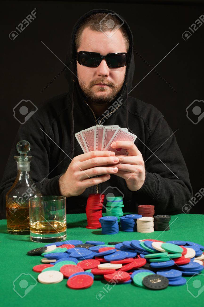 Photo of a hooded man playing poker while wearing sunglasses. Playing cards have been altered to be generic. Stock Photo - 12076263