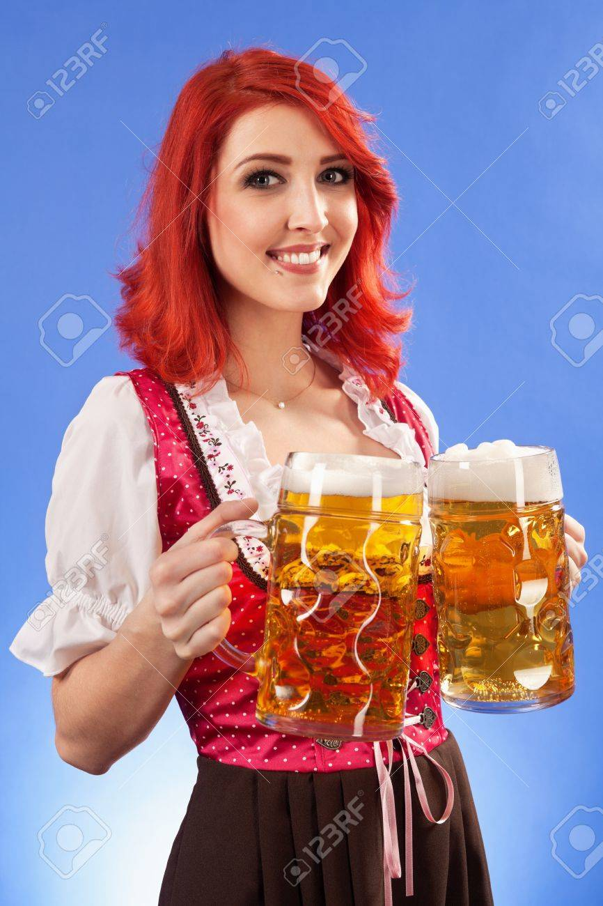 Photo of a beautiful female waitress wearing traditional dirndl and holding two mass beer steins. Stock Photo - 12893237