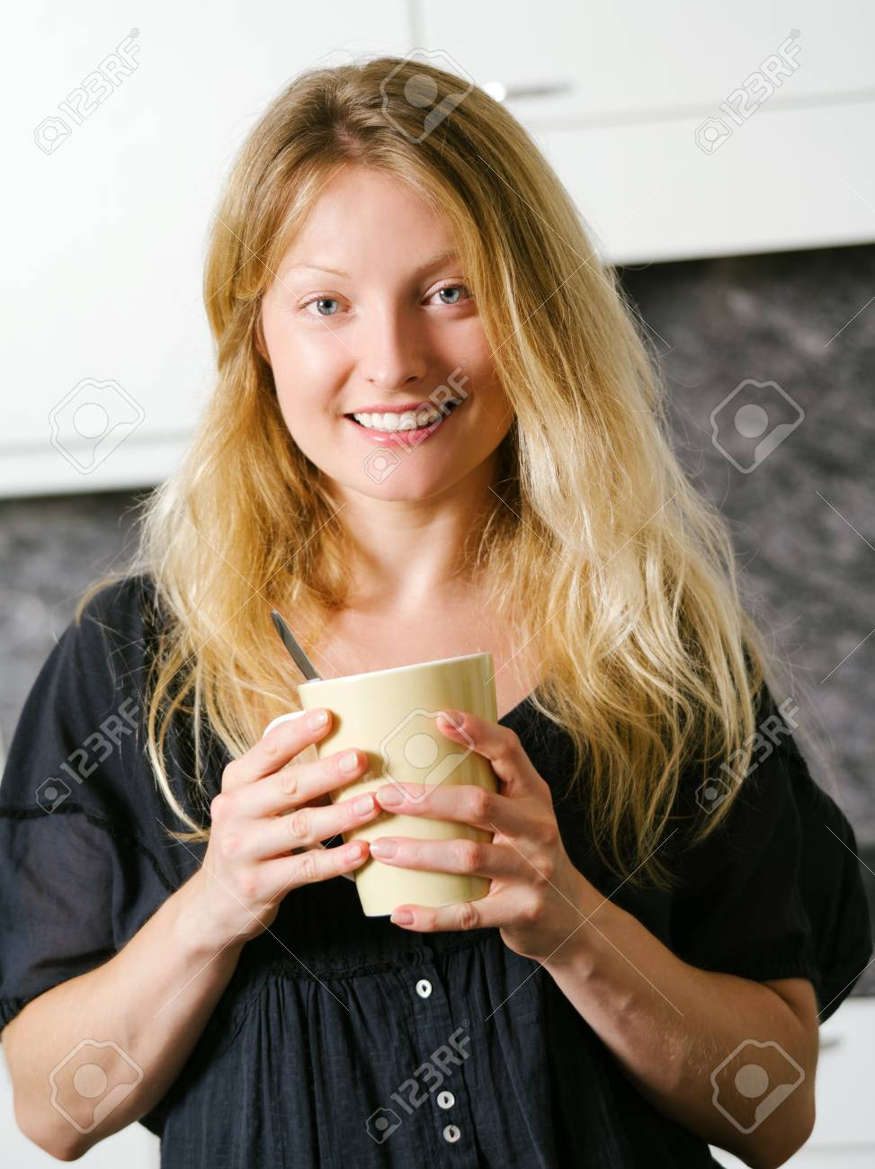 Photo of a beautiful smiling blond female in her kitchen holding a large coffee Stock Photo - 21383354