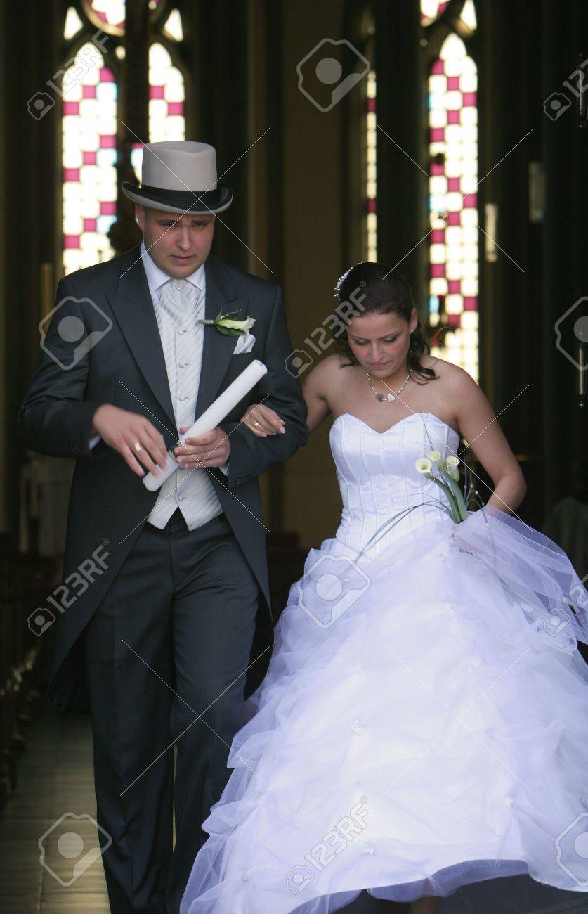 A wedding, bride and groom walking hand in hand out of church after ceremony Stock Photo - 3400162