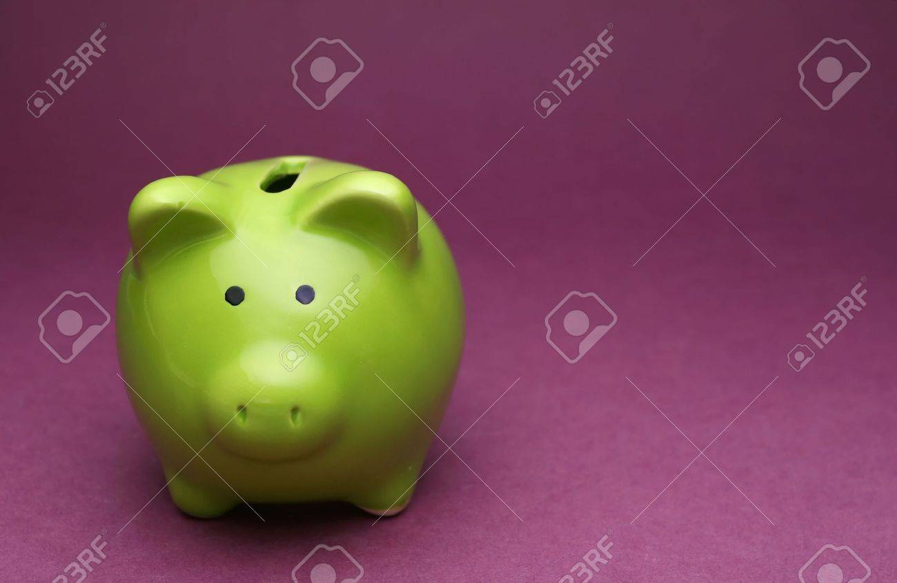 A green piggy bank on purple background, shot from the front Stock Photo - 1080674
