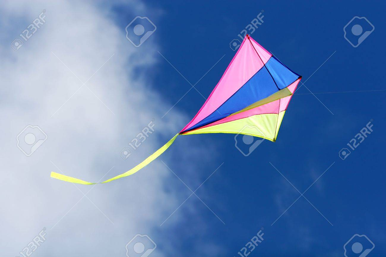 a kite flying against a blue sky in sunlight, bright colors and streaming tail - 1194975