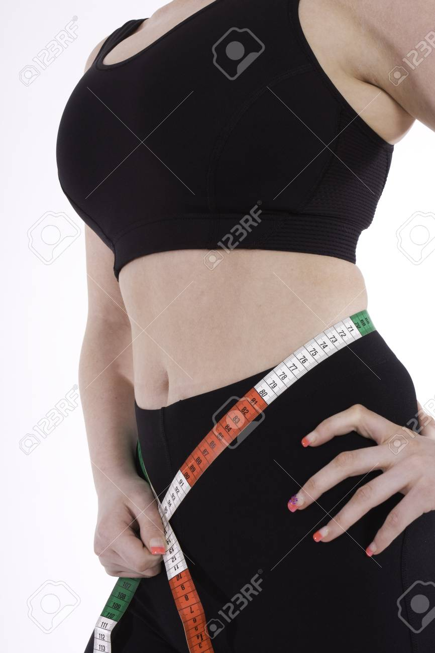 cropped shot of a young woman with a great figure measuring her waist Stock Photo - 9856618
