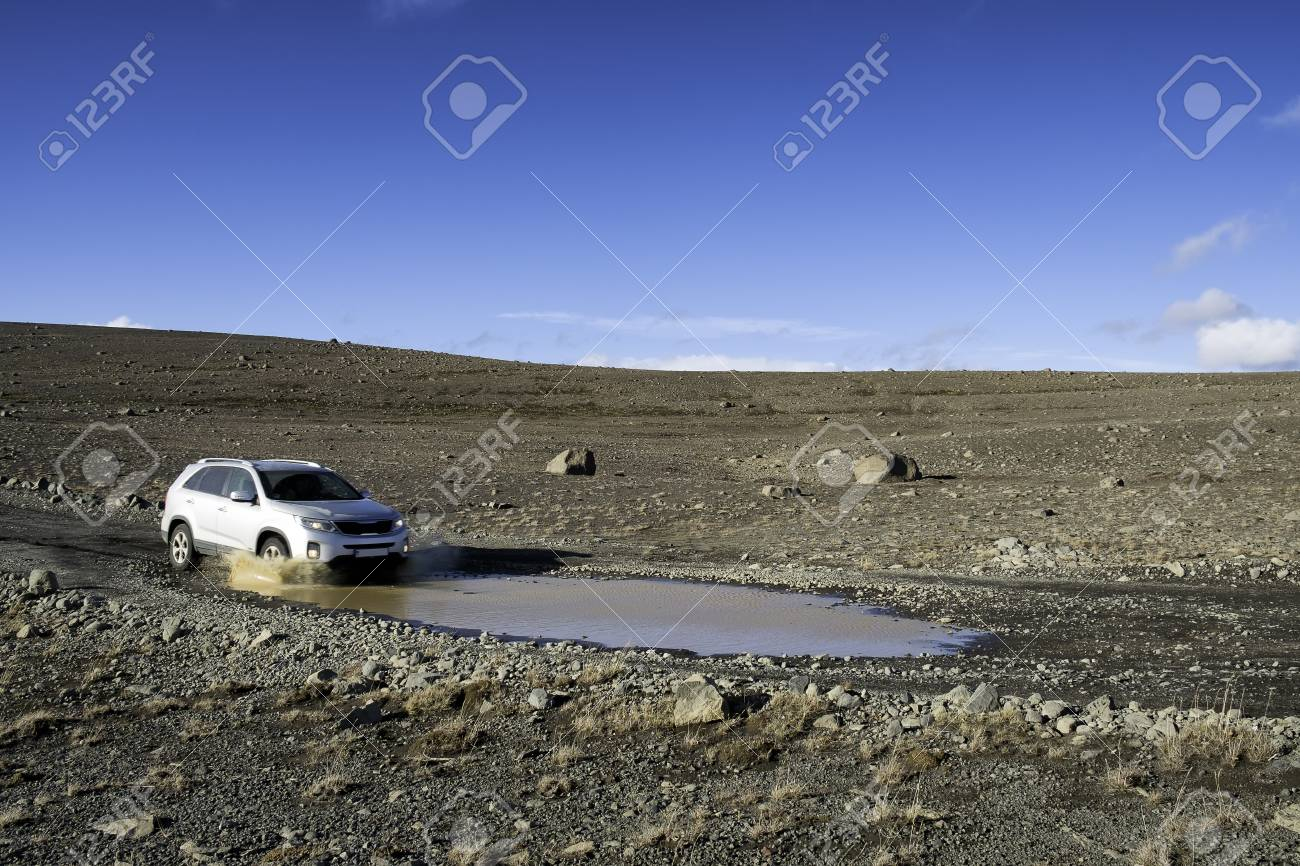 Paesaggi D Acqua Piscine 4x4 che viene guidato a velocità in un paesaggio desertico, circa a guidare  in una piscina di acqua sporca, cielo blu