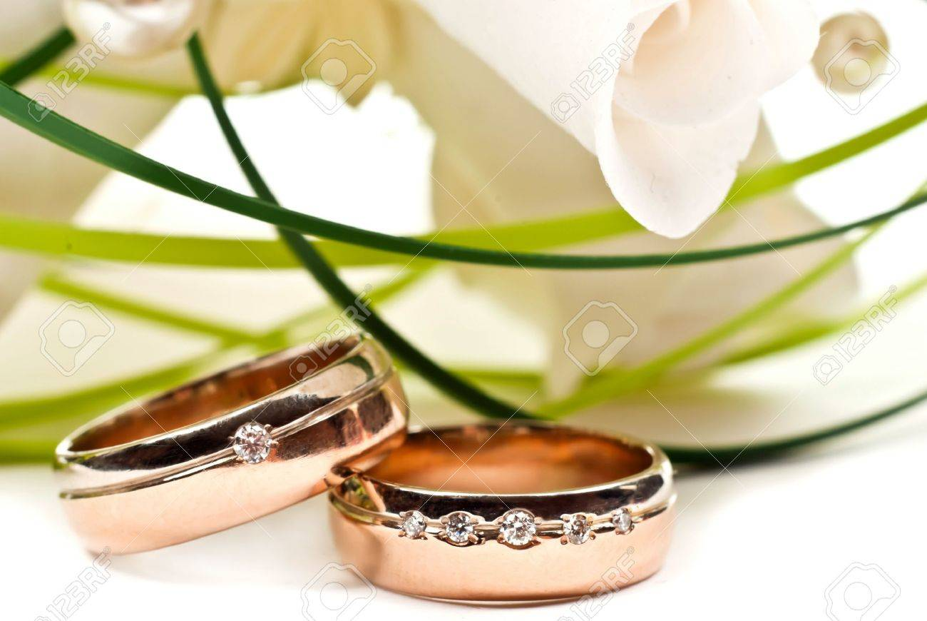 Pair of golden wedding rings with rose bouquet. Macro photo Stock Photo - 9612455