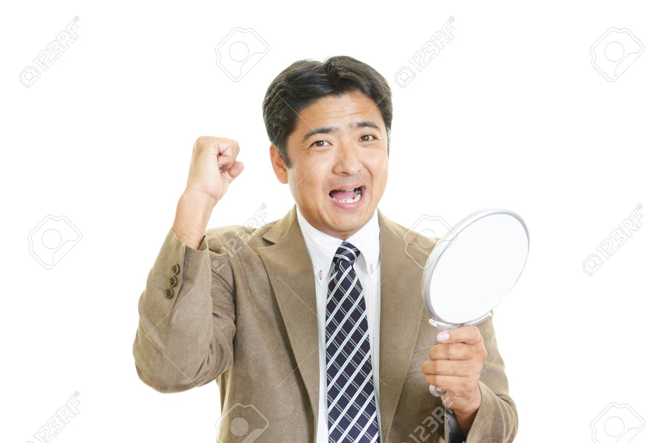 a man looking at himself in a hand mirror stock photo picture and