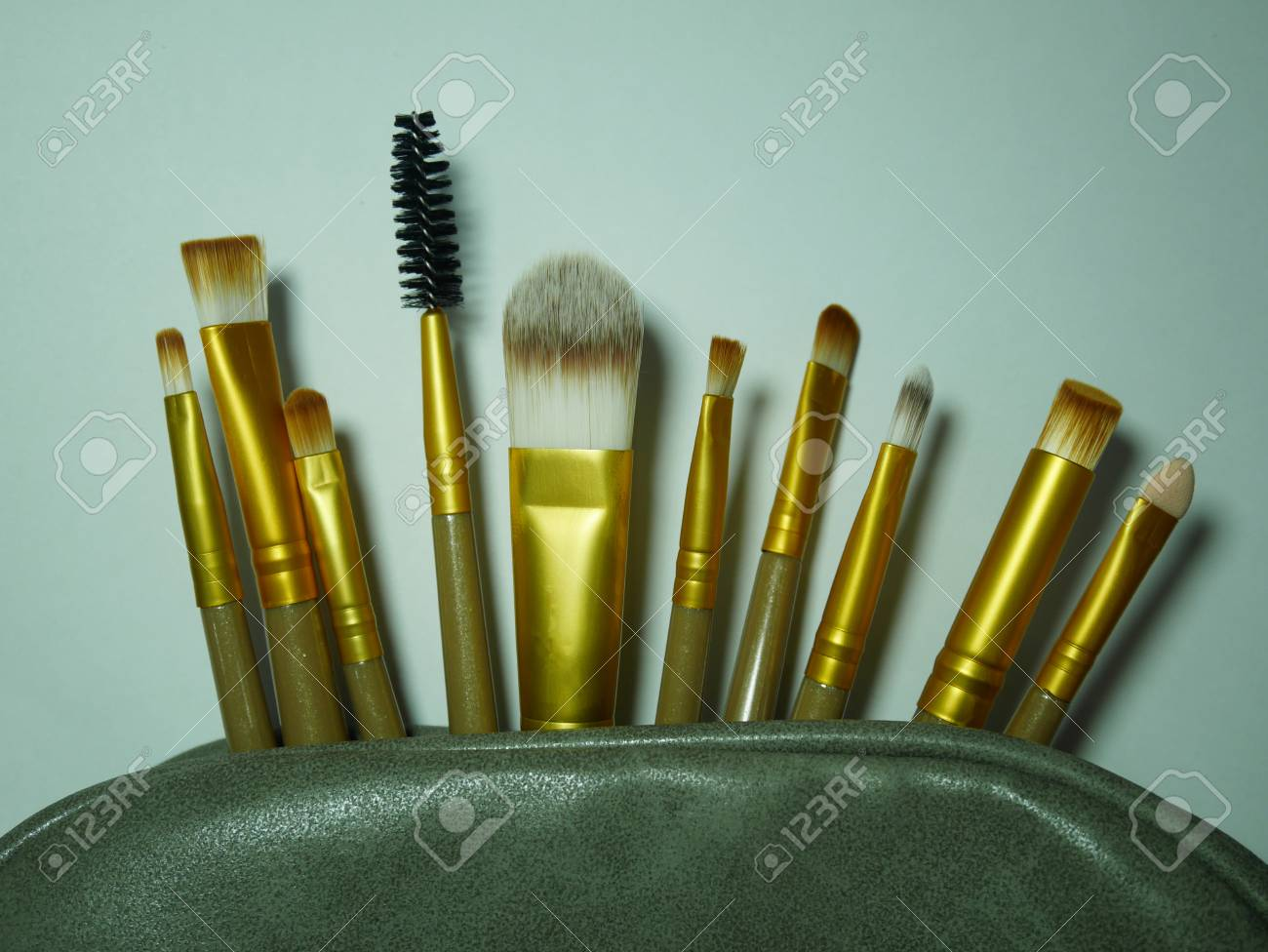 many brown and gold makeup brushes in the green cosmetic bag