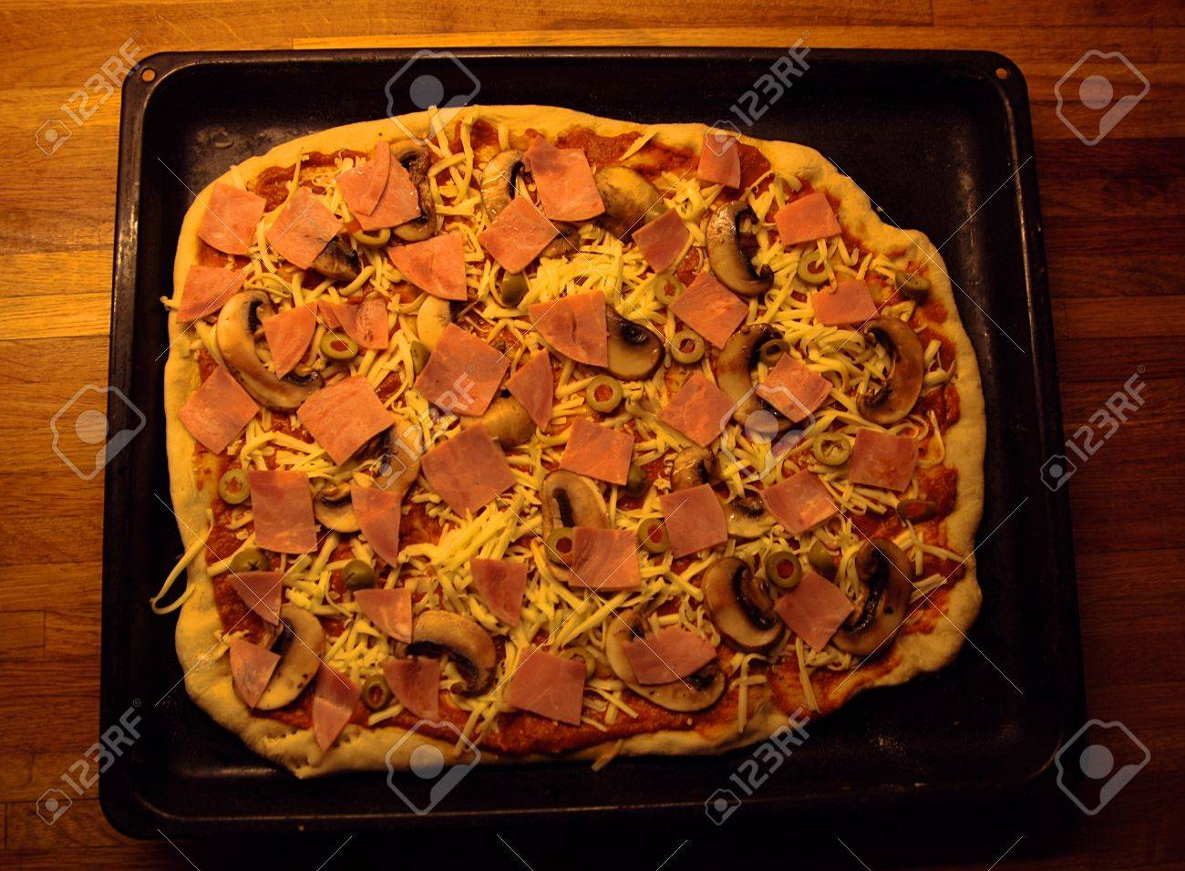 Tray with freshly made ham, mushroom and olive pizza Stock Photo - 12715175