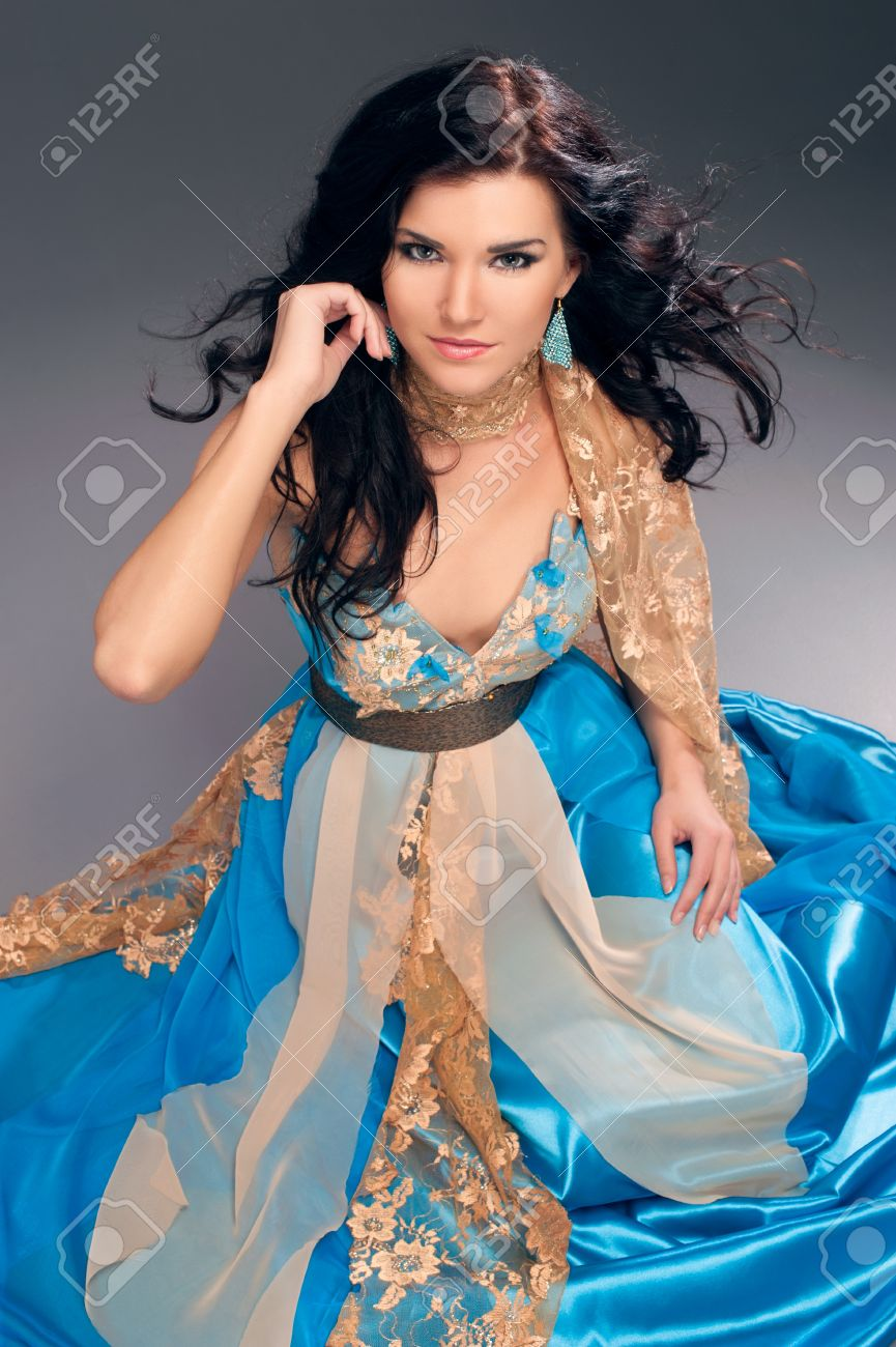 72672719802 beautiful Indian girl in a blue dress sitting on the floor Stock Photo -  21301224