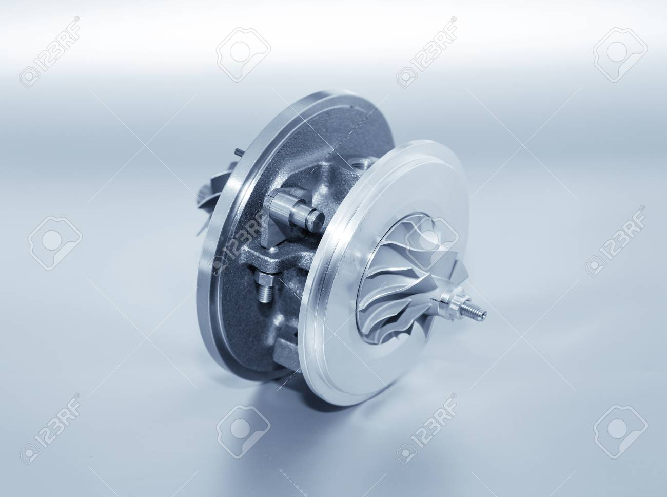 Turbocharger on metallic background. Car turbine - part of engine. Blue toned - 83734476