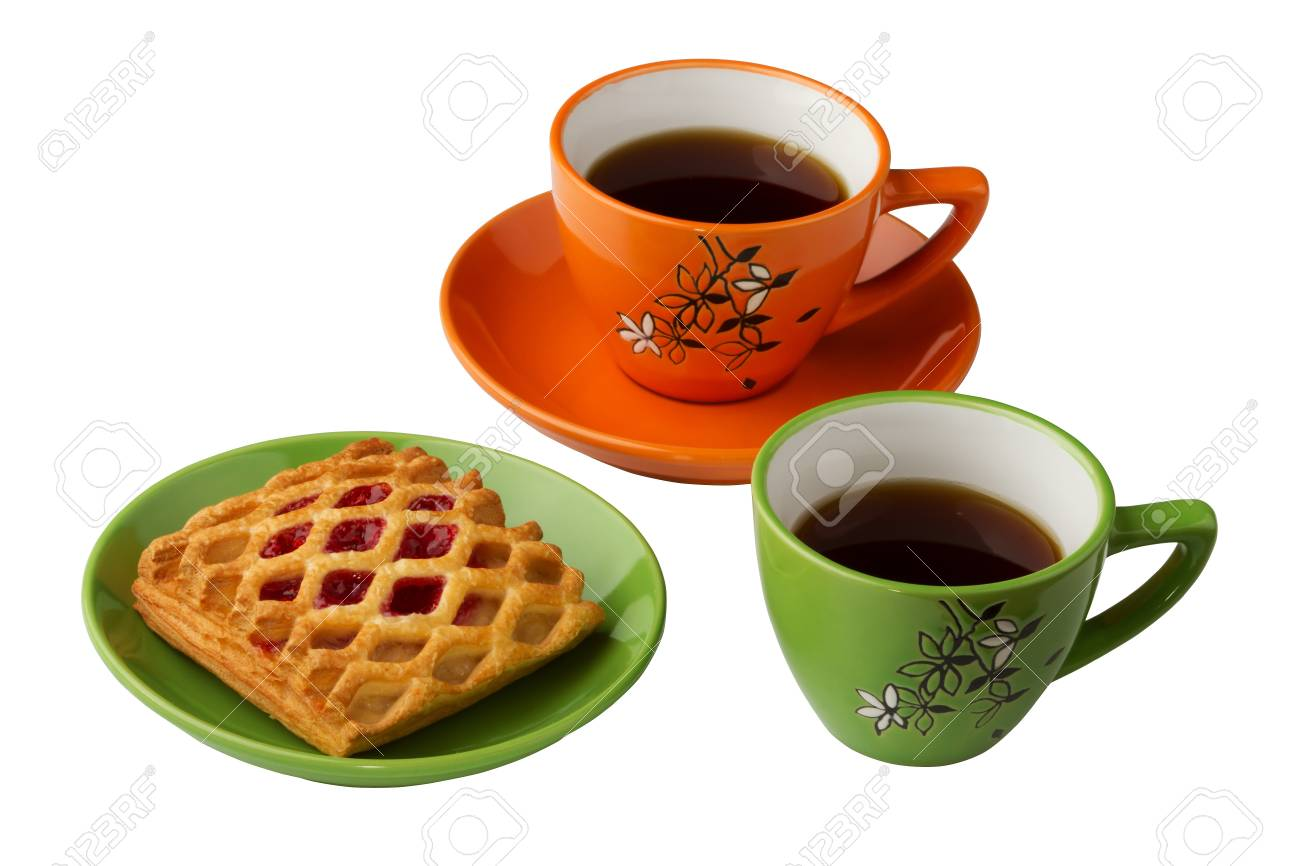 There are two cups with tea on the white background, orange and green. Also there are sweets on the saucer Stock Photo - 9587427