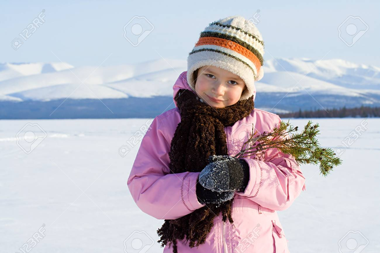 The girl with a branch of a fur-tree against mountains Stock Photo - 3705663