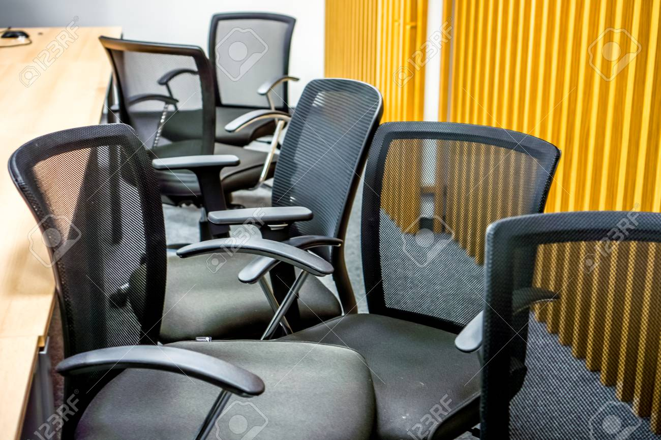 Many Black Office Armchairs Chaoticly Stands One By One Against Yellow Wall  With Vertical Lines.