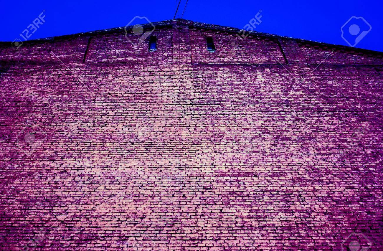 violet lilian pink brick wall with two small square dark windows