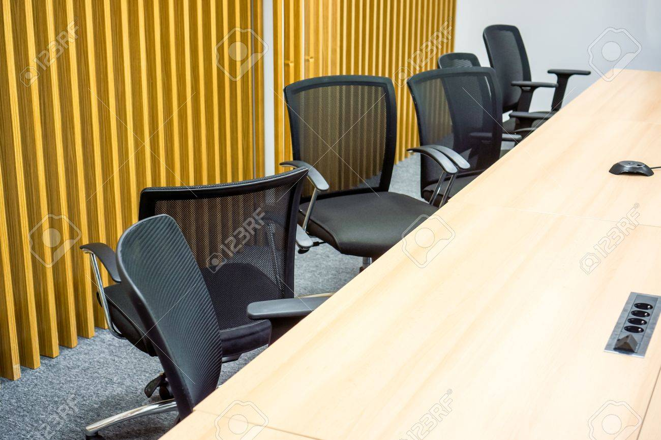 Big Wooden Table With Many Black Office Armchairs Chaoticly Stands One By  One Against Yellow Wall
