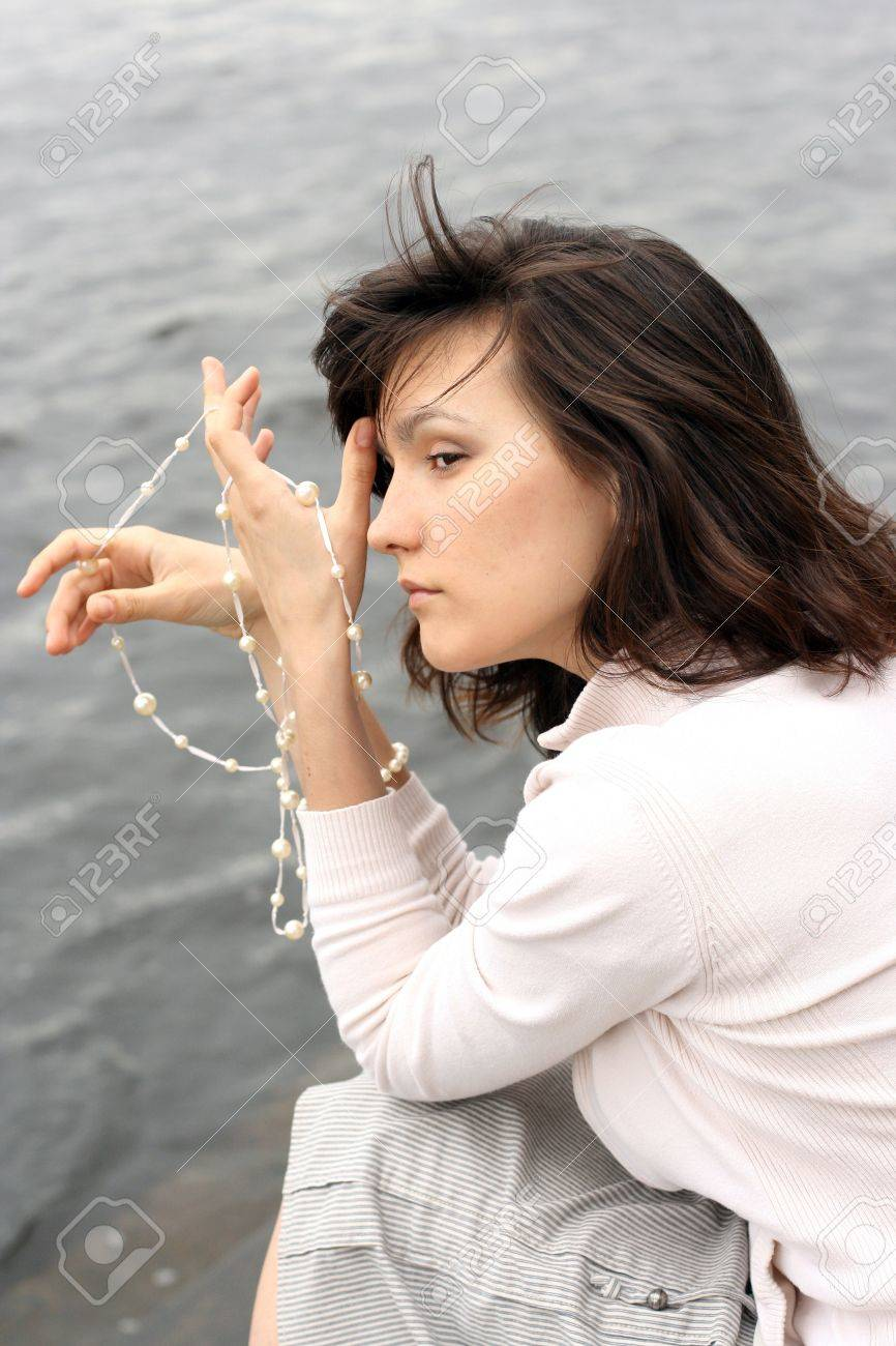 Portrait of beautiful woman with beads. She waiting somebody on the waterside. Stock Photo - 16084670