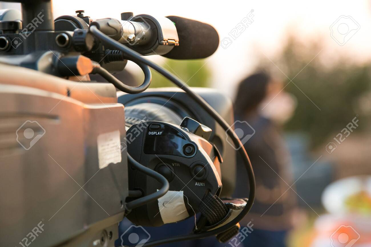 TV Camera and presenter host on a live news broadcast on location at sunrise - 149656801