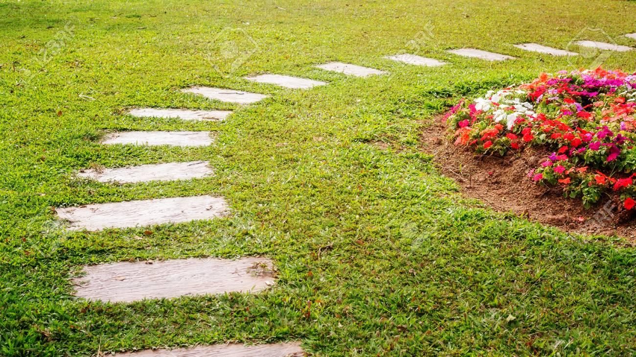 cement walkway in a flower garden. - 122180116