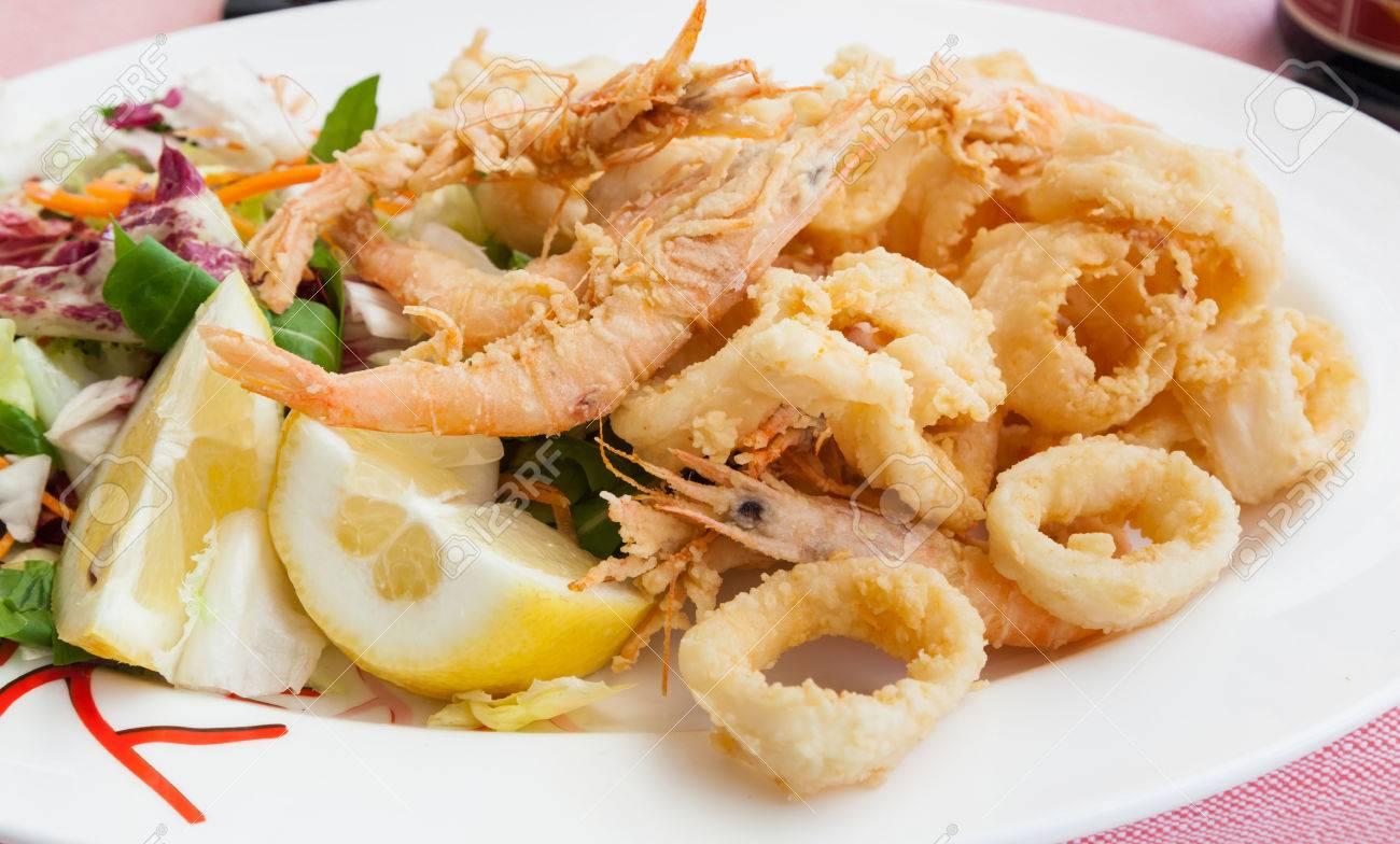 Fried shrimp and squid with lemon, italian food. - 34664441