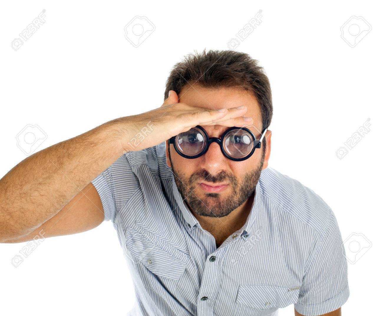 79cf2c8ebe Stock Photo - Young man with a surprised expression and thick glasses on white  background.