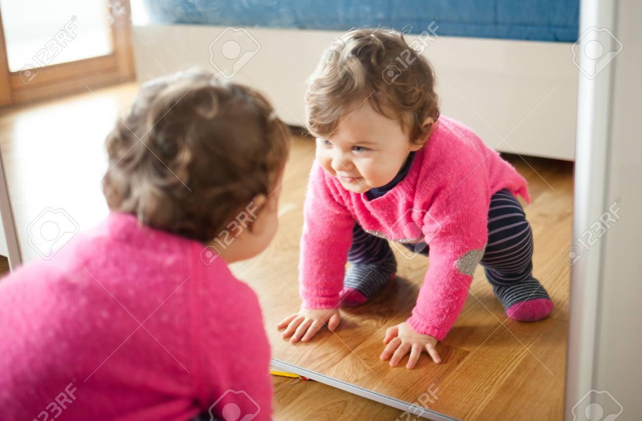 Enfant en bas âge bébé fille jouant avec un miroir dans la chambre.