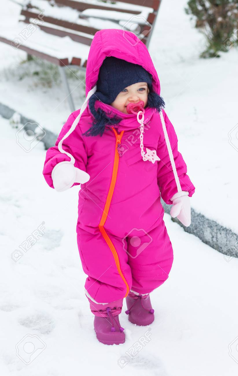 3c94adcab Adorable Toddler Baby Girl In A Magenta Snow Suit Playing On.. Stock ...