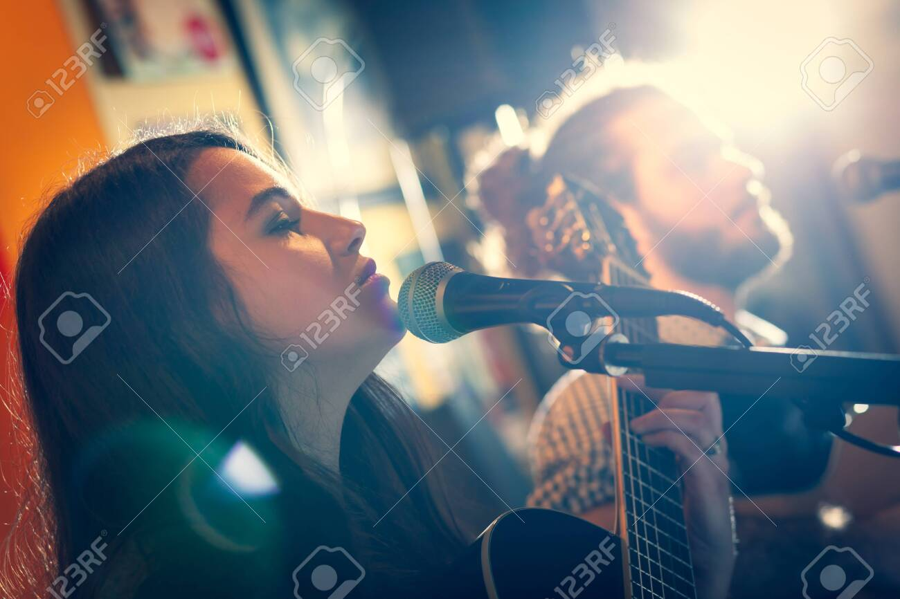 Duet of guitarists singing during a musical performance. Backlight with flare. - 120153496