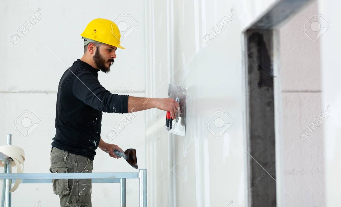 Interior construction, worker plastering gypsum board wall. - 120089173