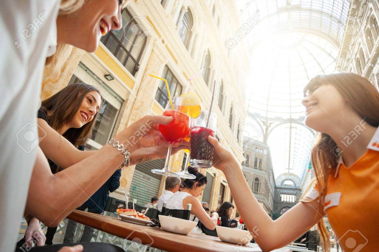 Friends do cheers with drinks in the gallery Umberto Primo in Naples. - 128332162