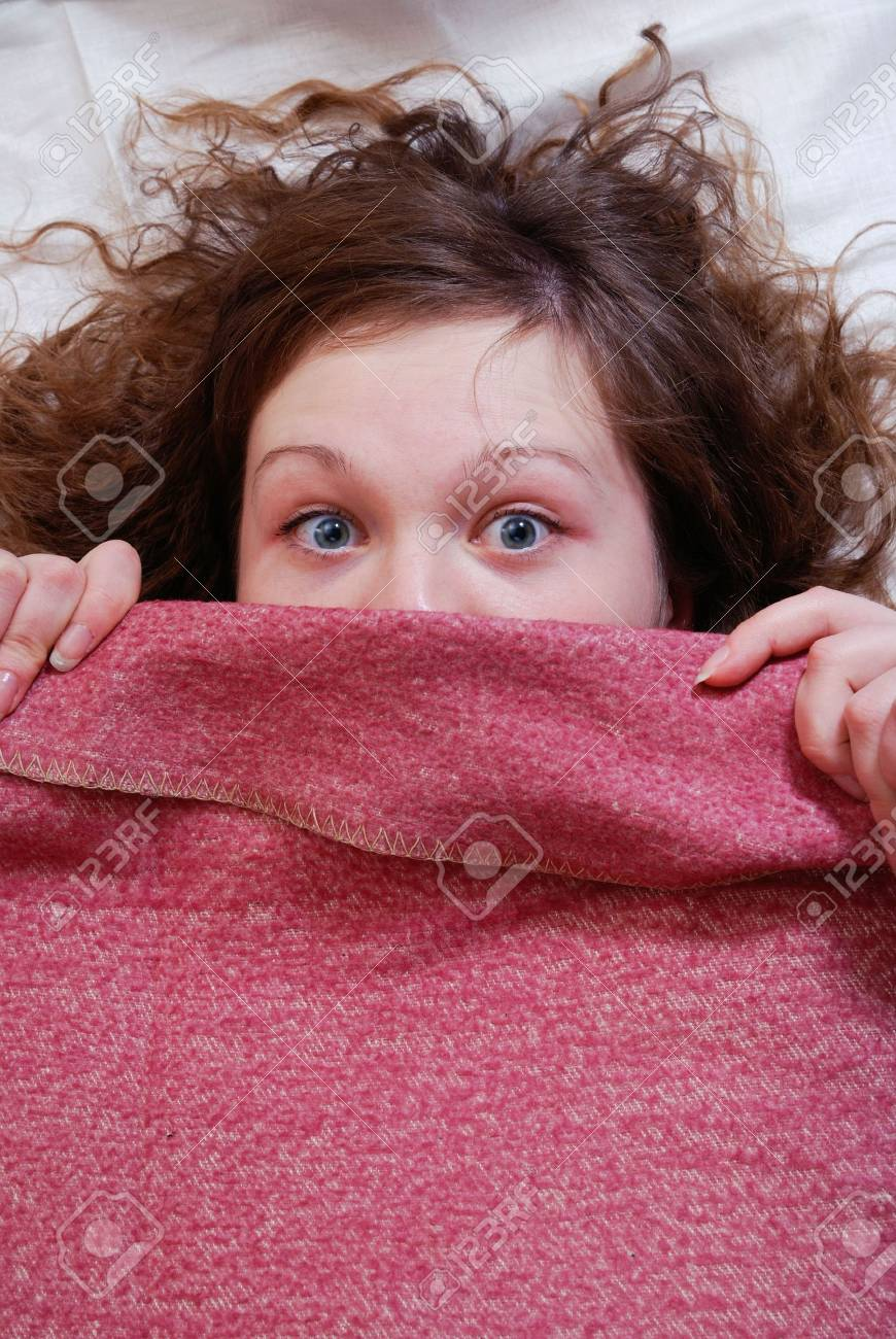 The young girl with the scared sight, closed by a blanket Stock Photo - 2263587