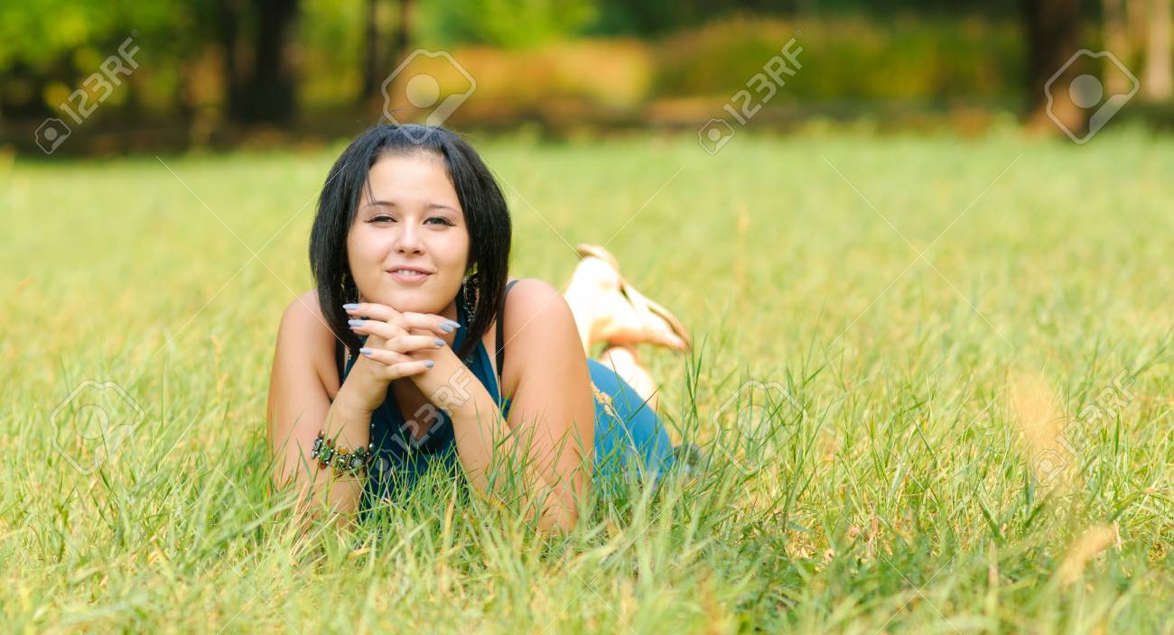Pretty girl relaxing outdoor on green grass Stock Photo - 7749161