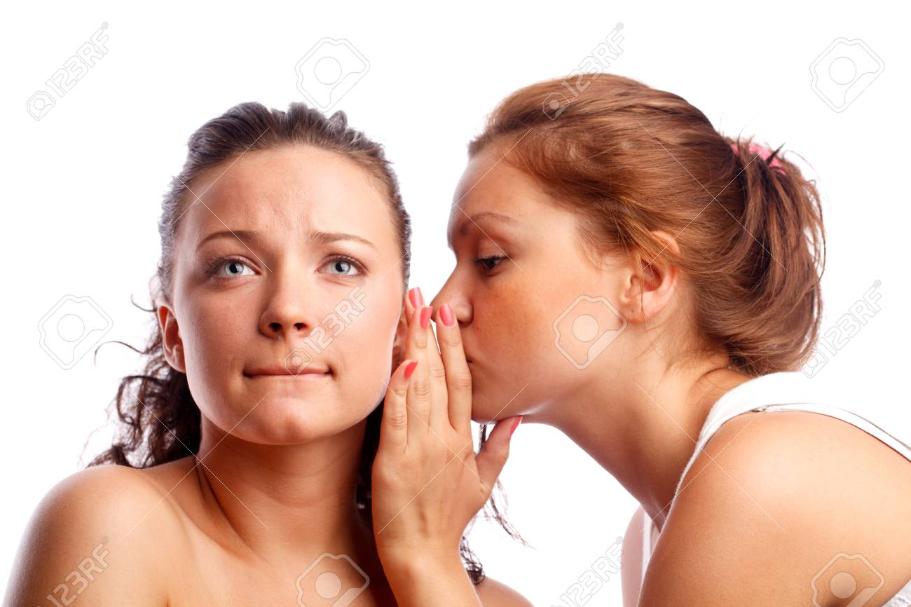 Young woman whispering something to her frind. Isolated over white. Stock Photo - 9754790