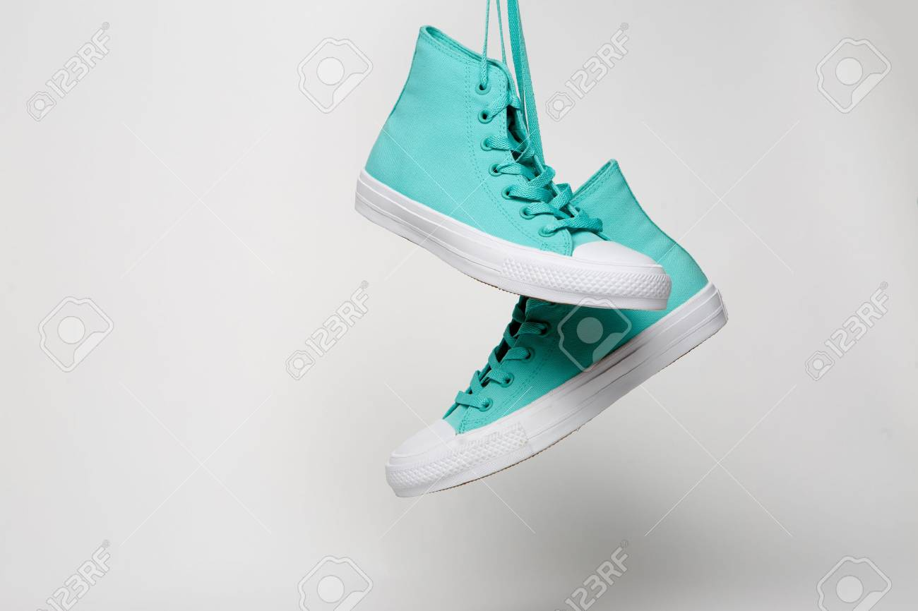 Blue Sport shoes hanging on laces on white background