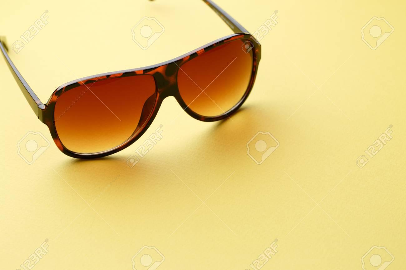 Foto de archivo - Gafas de sol en fondo amarillo vacío con lugar para  publicidad 82050cd34834