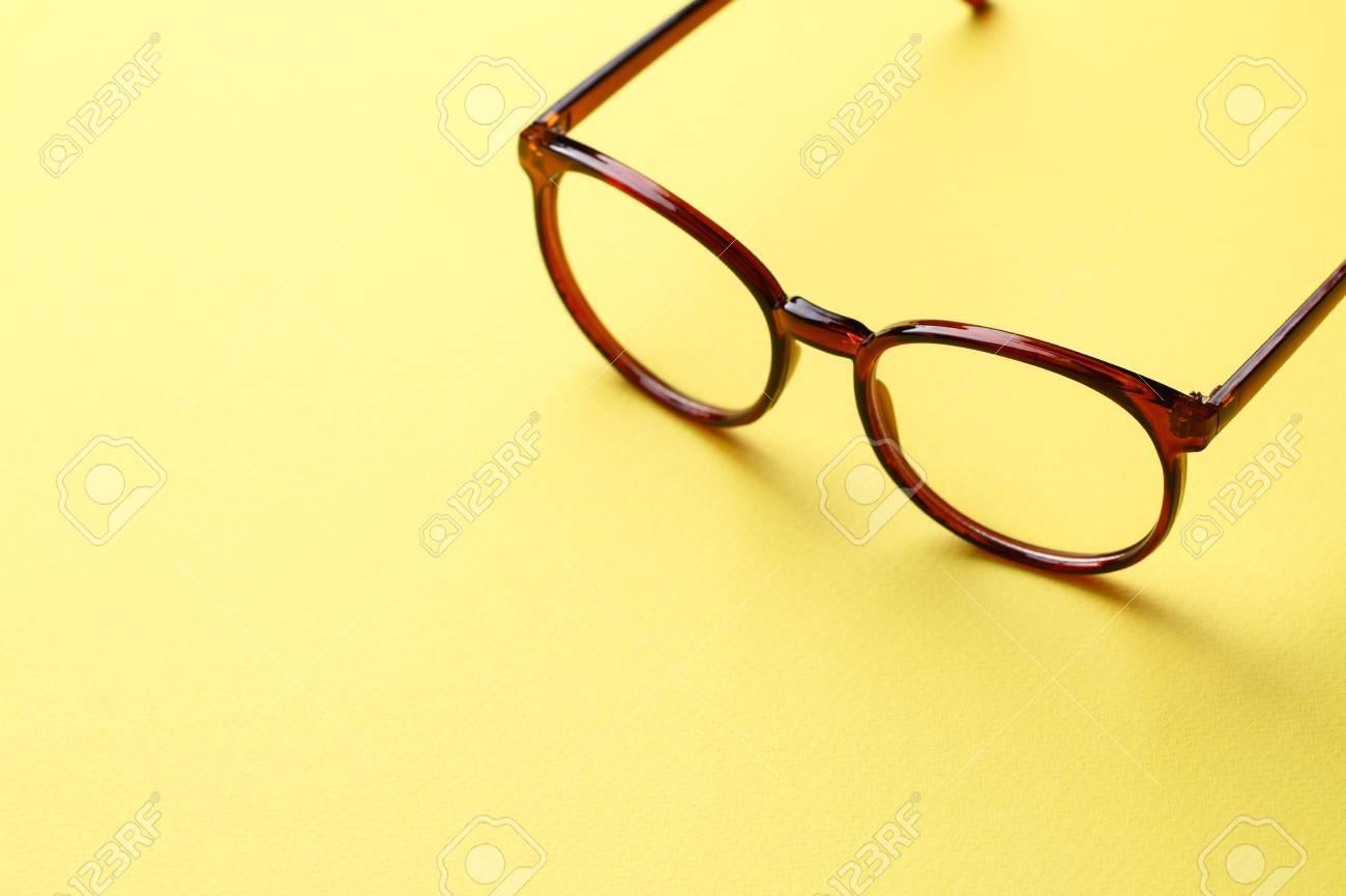 0473fc23 Gafas marrones con lentes transparentes sobre fondo amarillo vacío