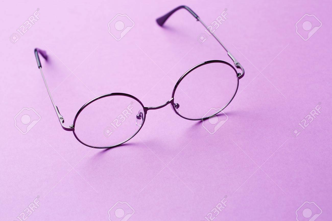 Foto de archivo - Gafas redondas con lentes transparentes sobre fondo morado  vacía 1dc9b75aef88