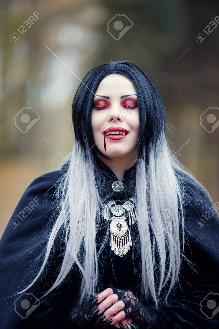 Image of gothic vampire girl with eyes closed with blood at mouth