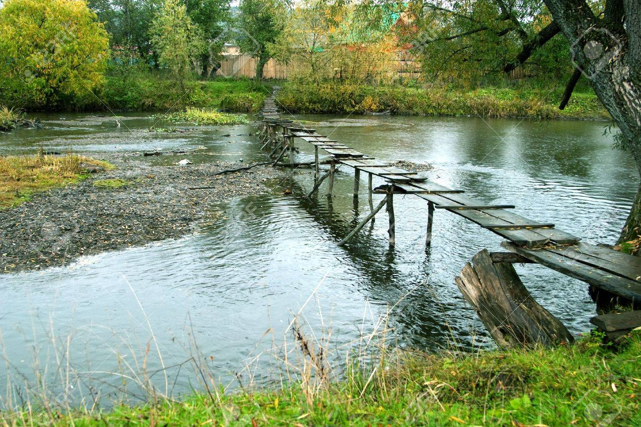 Autumn landscape: the river and the old wooden footbridge. Gloomy weather Stock Photo - 5678682